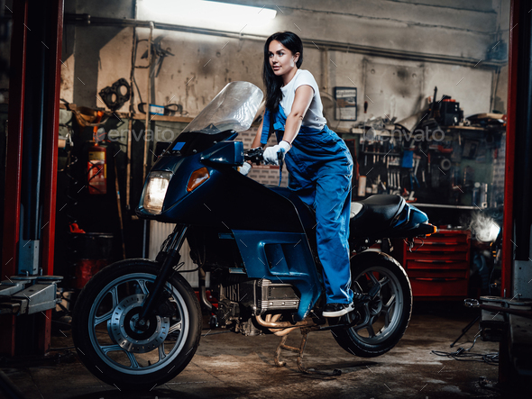 Young female mechanic in blue overalls posing on sportbike in garage or workshop - Stock Photo - Images