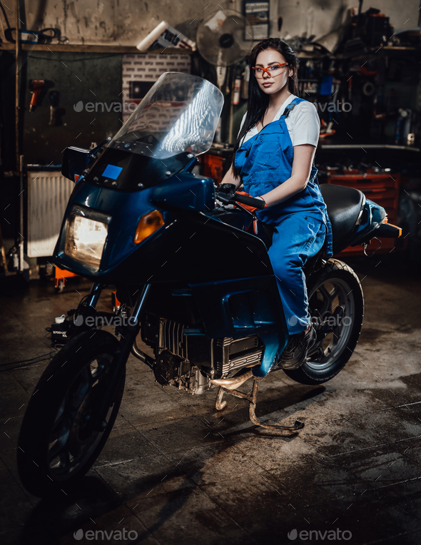 Young brunette female mechanic in blue overalls sitting on sportbike in garage or workshop - Stock Photo - Images