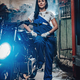 Beautiful brunette woman in blue overalls posing next to a custom bobber in garage or workshop - PhotoDune Item for Sale