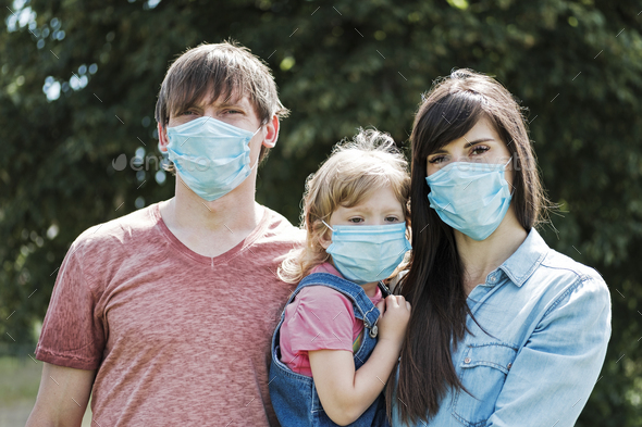 Young family with daughter wearing face masks - Stock Photo - Images