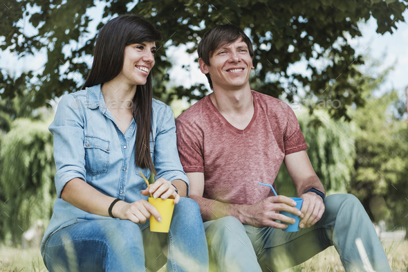 Young happy couple relaxing in the shade of a tree - Stock Photo - Images
