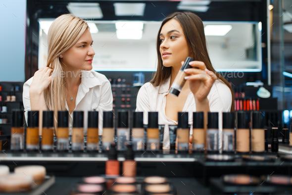 Cosmetician and woman choosing nail varnish - Stock Photo - Images