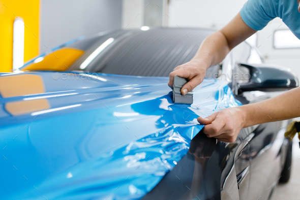 Car wrapping, mechanic with squeegee installs film - Stock Photo - Images