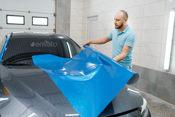 Car wrapper holds protective foil or film roll - Stock Photo - Images