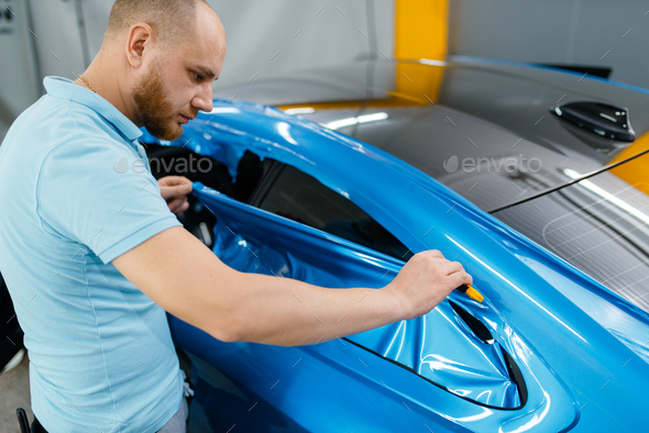 Car wrapping, mechanic cuts vinyl foil or film - Stock Photo - Images