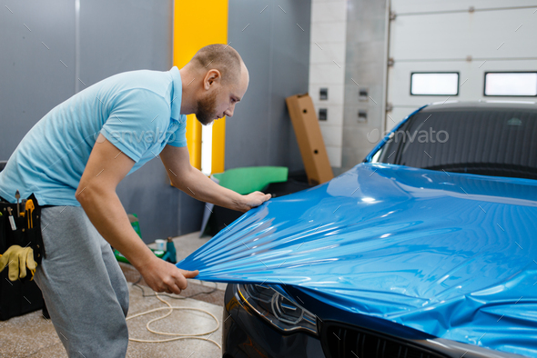Car wrapper puts protective foil or film on hood - Stock Photo - Images
