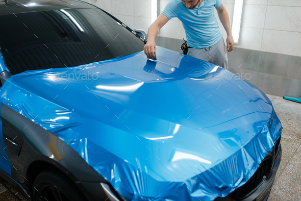 Car wrapping, man with squeegee installs film - Stock Photo - Images