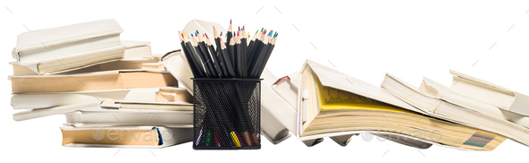 Colored pencils in a pencil pot and stacks of books. Isolate - Stock Photo - Images