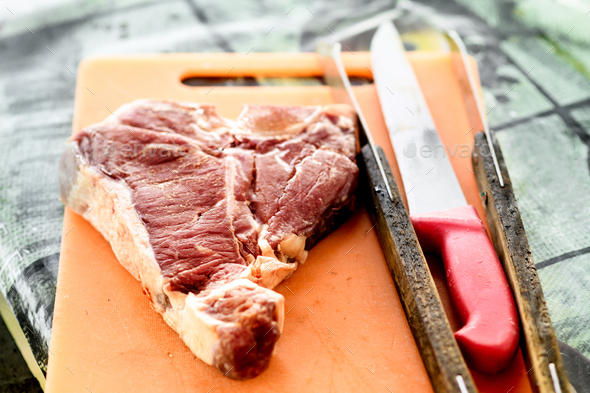 Raw Florentine beef steak on a cutting board - Stock Photo - Images