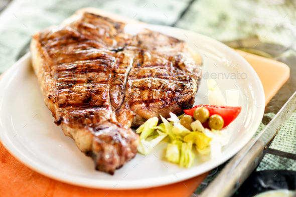 Grilled or barbecued Florentine steak on a plate - Stock Photo - Images