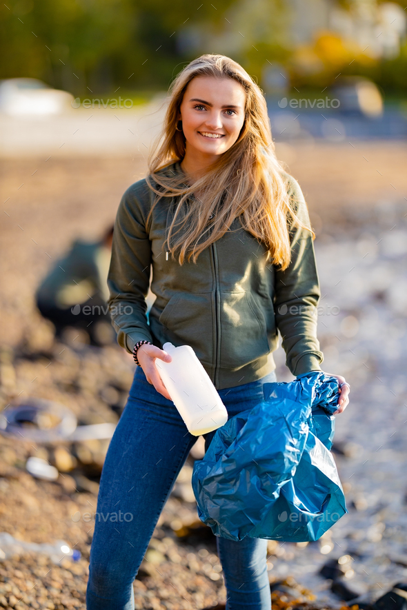 Smiling female volunteer holding bottle and garbage bag at beach - Stock Photo - Images