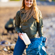 Smiling female volunteer holding bottle and garbage bag at beach - PhotoDune Item for Sale