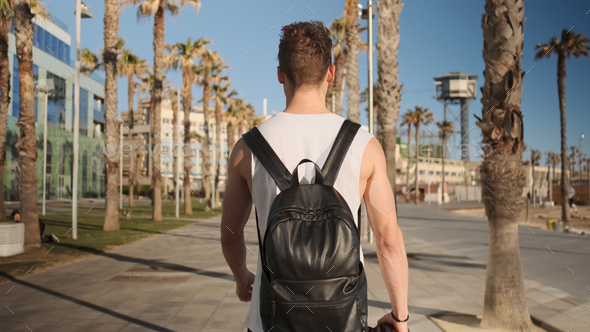 Back view of attractive guy with backpack walking along seaside after training outdoor - Stock Photo - Images