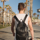 Back view of attractive guy with backpack walking along seaside after training outdoor - PhotoDune Item for Sale