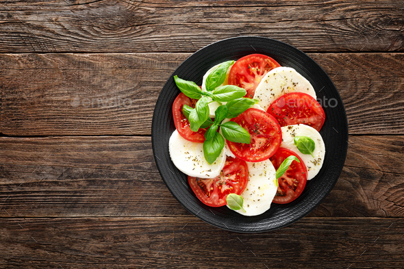 Caprese salad. Salad with mozzarella cheese, fresh tomatoes, basil leaves and olive oil - Stock Photo - Images