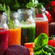 Four kind of vegetable juices: red, burgundy, orange, green, in small glass bottles - PhotoDune Item for Sale