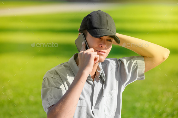Trendy young teenage boy using his smartphone - Stock Photo - Images