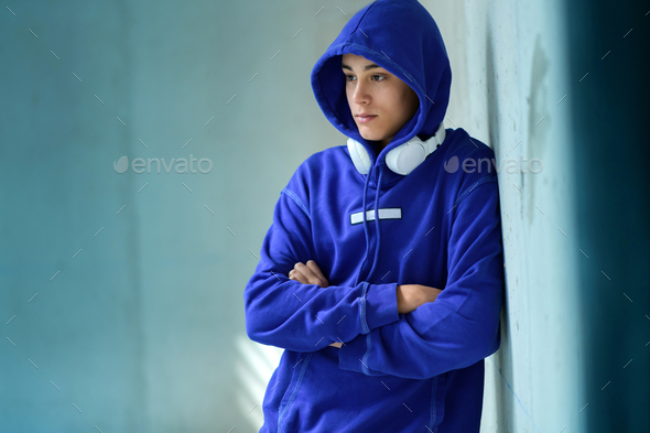 Thoughtful serious teenage boy in a blue hoodie - Stock Photo - Images