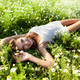 Young sexy brunette woman lying on grass and flowers and smiling on summer day with green nature and - PhotoDune Item for Sale