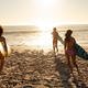 Young mixed race people holding surf boards on beach - PhotoDune Item for Sale