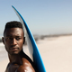 African American man holding surf board on the beach - PhotoDune Item for Sale