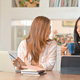 Two young female students talk with a smile and drink coffee while creating a report. - PhotoDune Item for Sale