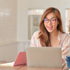 Woman wearing glasses is using a laptop and smiling happily. - PhotoDune Item for Sale