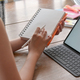 Woman holding a notebook with a pen and laptop on the table. - PhotoDune Item for Sale