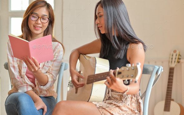 Two young women playing guitar and singing happily. - Stock Photo - Images