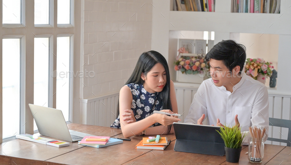 Young men and young women are using laptop and helping to make reports. - Stock Photo - Images