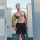 Natural portrait of young athletic shirtless man standing near concrete wall. - PhotoDune Item for Sale
