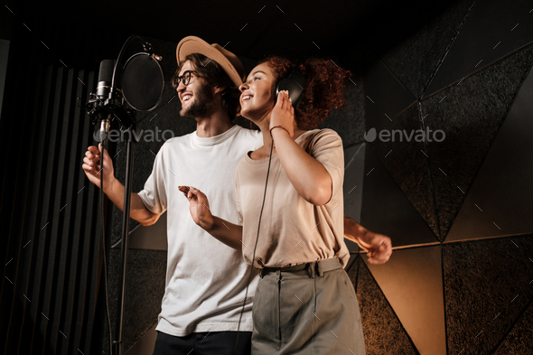 Young attractive man and woman joyfully singing together in modern sound recording studio - Stock Photo - Images