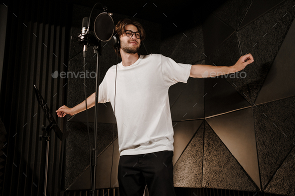 Young attractive male singer in headphones dancing during record new song in modern sound studio - Stock Photo - Images