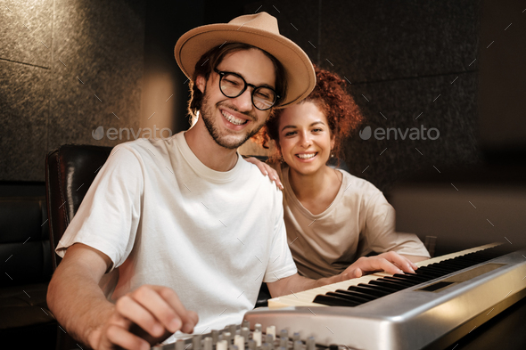 Cheerful musicians happily looking in camera recording song on piano keyboard for new music album - Stock Photo - Images