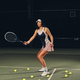 Female tennis player in action in a tennis court indoor. - PhotoDune Item for Sale