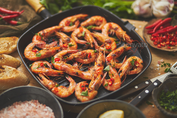 Tasty appetizing roasted shrimps prawns with spices on pan with ingredients on rusty background - Stock Photo - Images