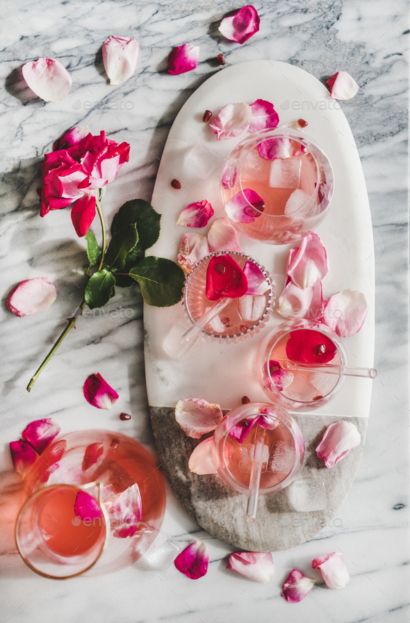 Rose lemonade with ice and rose petals over marble background - Stock Photo - Images