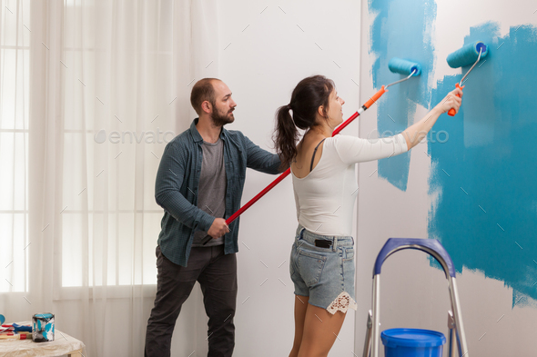 Young couple painting the wall - Stock Photo - Images