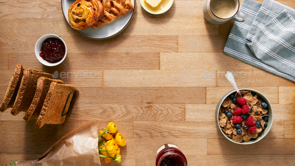 Overhead Flat Lay Shot Of Table Laid For Breakfast With Toast Cereal Croissant Pastries And Flowers - Stock Photo - Images