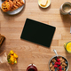 Overhead Flat Lay Of Digital Tablet On Table Laid For Breakfast With Cereal Croissant And Flowers - PhotoDune Item for Sale