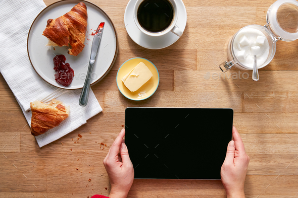 Overhead Flat Lay Of Woman With Digital Tablet On Table Laid For Breakfast With Croissant And Coffee - Stock Photo - Images