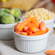 Frozen vegetables such as baby carrot and and Brussels sprouts in the bowls on the kitchen table - PhotoDune Item for Sale