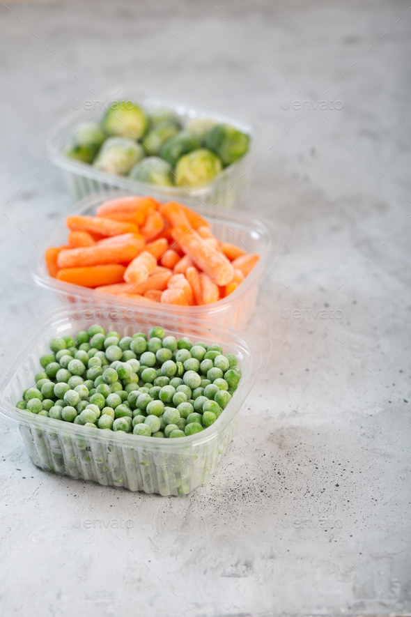 Frozen vegetables such as green peas, brussels sprouts and baby carrot in the storage boxes - Stock Photo - Images