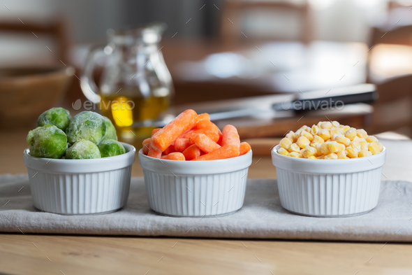 Frozen vegetables in the bowls on the kitchen table, horizontal - Stock Photo - Images