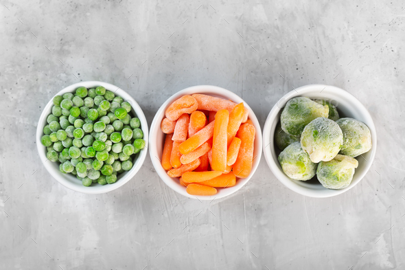 Frozen vegetables such as green peas, brussels sprouts and baby carrot in the white bowls - Stock Photo - Images