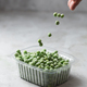 Falling frozen green peas in the storage box on the kitchen table, vertical orientation - PhotoDune Item for Sale