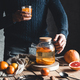 A man pours citrus tea on a wooden table. Healthy drink, vintage style. Vegan, eco products - PhotoDune Item for Sale