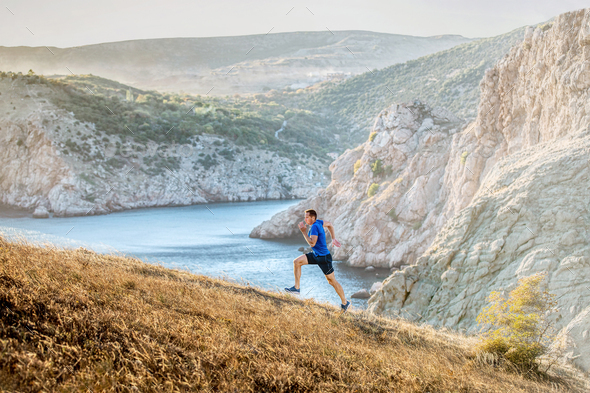 middle-aged man running uphill on trail - Stock Photo - Images
