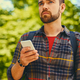 A man talks by a smart phone in a park. - PhotoDune Item for Sale