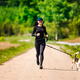 Sport girl is running with a dog (Beagle) on the rural road towadrds camera. - PhotoDune Item for Sale